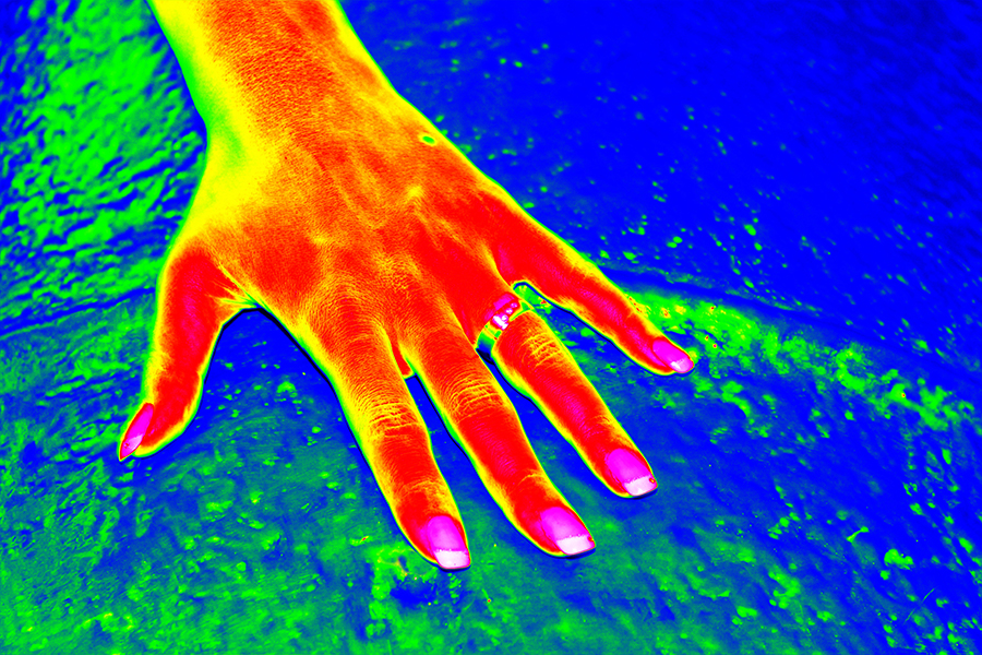 Infrared thermovision image of woman hand over the cold water